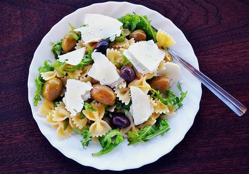 Pasta butterflies (farfalle) with mozzarella, olives and salad, Italian dish