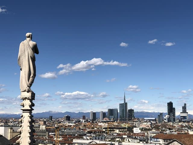 Milan - ancient statue overlooking modern city skyline
